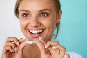 pretty woman smiling holding whitening tray