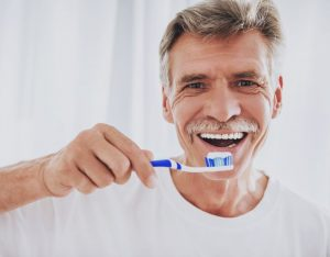 older man brushing teeth and preventing dental implant infections in Jacksonville